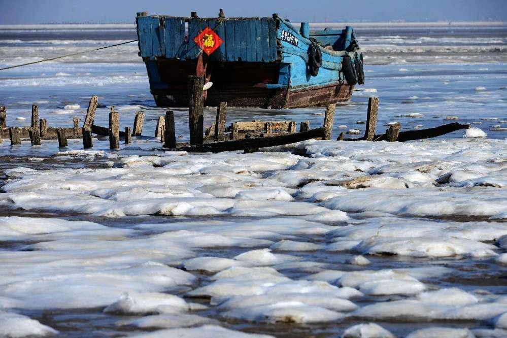 胶州湾海域出现大面积海冰 渔船被冻浅滩