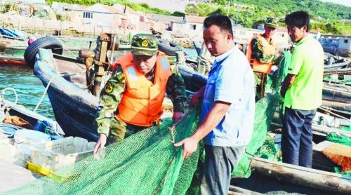 8月31日,山东青岛薛家岛边防派出所帮助准备出海捕鱼的渔民拉网.