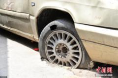 郑州一僵尸车十几年未挪窝 轮被砌进水泥地