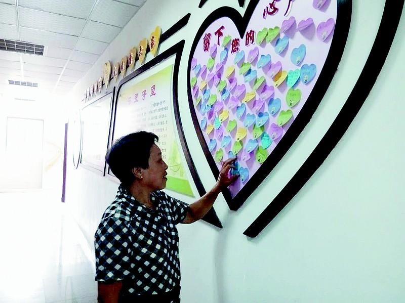 """看到一个很大心形围成的""""民意墙"""",上面贴满了各种颜色的心形的便利贴图片"""
