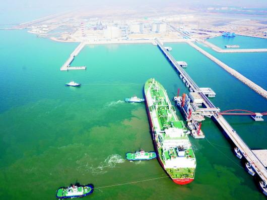 董家口港区LNG接收站码头。 因港兴城的青岛最知晓港口对于城市发展的意义,港口的内涵不断延伸。2009年6月,随着青岛港通过能力趋于饱和,董家口港项目逐步提上日程,正式开工建设。依托于港口,作为青岛市和西海岸新区重点功能区的董家口经济区也应运而生,开启了它的快速发展之路。经过近9年的发展,如今,一座全新的绿色新港城已经崛起,并成为青岛迈向世界的新一极。 在十九大报告中明确指出,十八大以来我国经济建设取得重大成就,其中港口等基础设施建设快速推进,在供给侧结构性改革深入推进、不断优化经济结构中起到了重要的